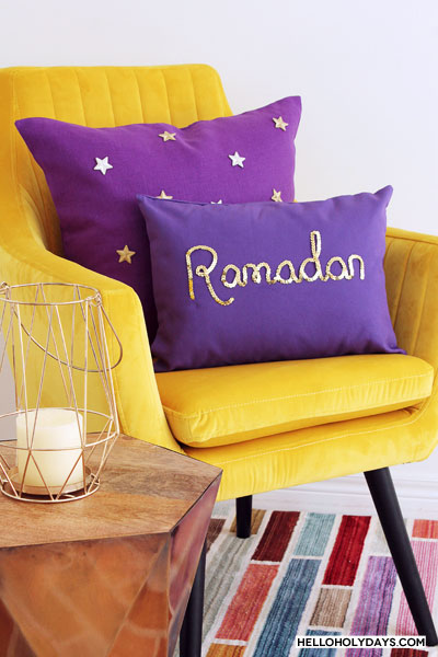 "Manal Aman shows how to make DIY throw pillows for Ramadan and Eid on Hello Holy Days! In this photo, a purple canvas pillow with ""Ramadan"" written in gold sequins and a purple linen pillow with gold star appliques are shown on a yellow velvet chair."