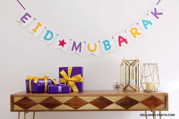 "A DIY ""Eid Mubarak"" garland hangs over a HomeSense console table with gifts."