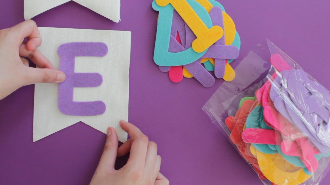Applying felt alphabet stickers onto bunting for a DIY Eid garland.